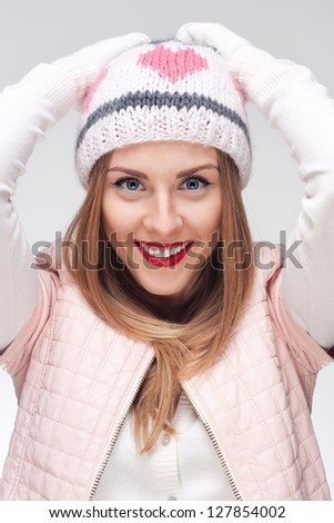 Young smiling woman with funny hat and raised hands - stock photo