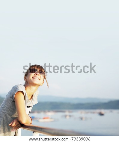 Young smiling woman with glasses outdoor portrait on blue airy background with copyspace - stock photo
