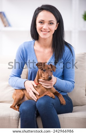 Young smiling woman with her cute dog. - stock photo