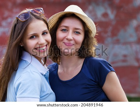 Young smiling woman with her teen daughter outdoors - stock photo
