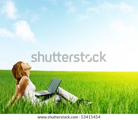 Young smiling woman with laptop sitting in meadow with green grass - stock photo