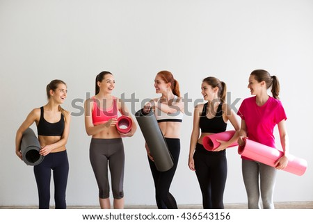 Young smiling woman with mats after yoga class.
