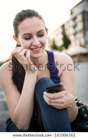 Young smiling woman with mobile phone - stock photo