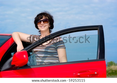 Young smiling woman with red car - stock photo