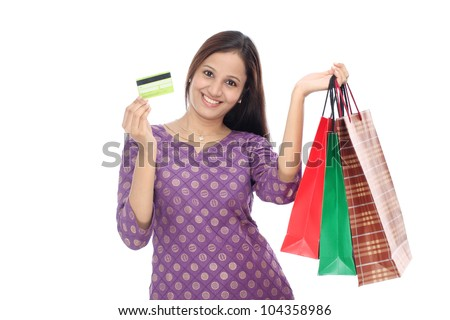 Young smiling woman with shopping bags and credit card - stock photo
