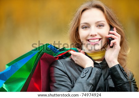 Young smiling woman with shopping talking on a mobile phone - stock photo