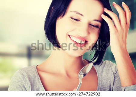 Young smiling woman with spoon. - stock photo