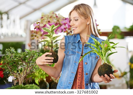 Young smiling woman with two kokedama in her hands in a garden center - stock photo