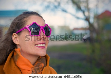 Young smiling woman with vivid emotions in sunglasses in the form of a star