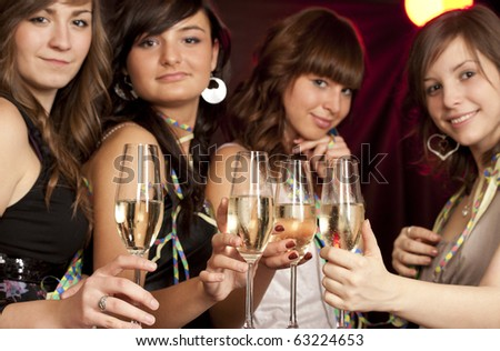 Young smiling women with glasses of champagne - stock photo