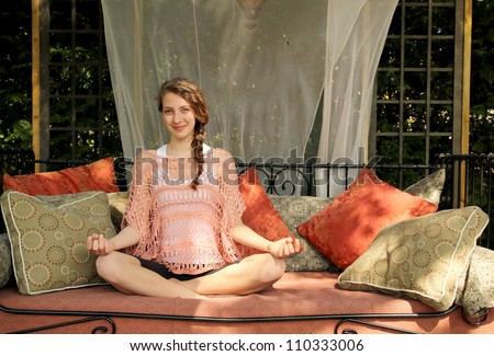 Young smling girl doing yoga on a couch outside