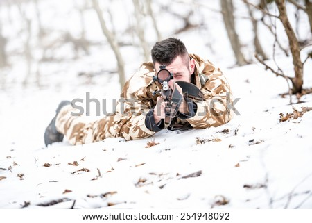 Young sniper aiming through scope and shooting with rifle during operation - war concept or hunting concept - stock photo