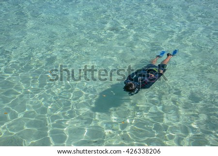 Young snorkeling in clean water over coral reef, Time to snorkeling in Maldives Beach Island resort.