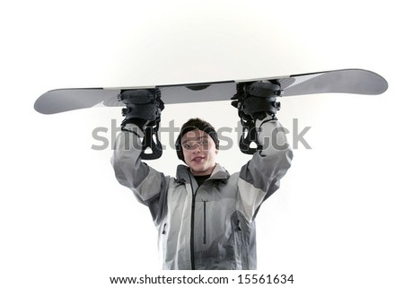 Young snowboarder holding board over head - stock photo
