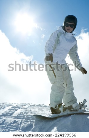 Young snowboarder standing on top of hill, looking at camera, full length portrait