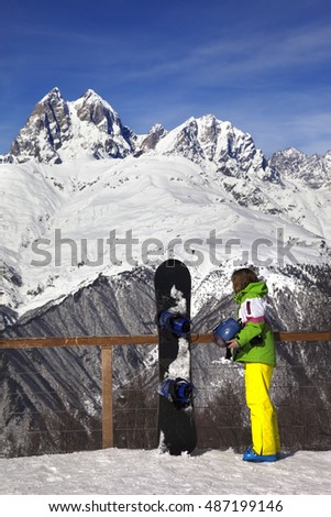 Young snowboarder with helmet in hands and snowboard on viewpoint in winter mountain at sun day. Caucasus Mountains. Hatsvali, Svaneti region of Georgia.