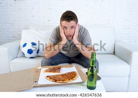young soccer fan in stress watching football game on television sitting at home living room sofa couch with pizza box and beer bottle enjoying the match looking nervous and excited - stock photo