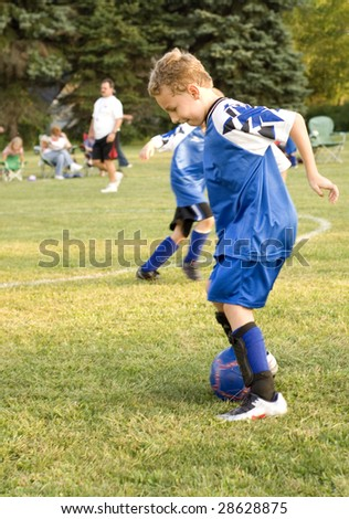 Young soccer player dribbling ball on field during game - stock photo
