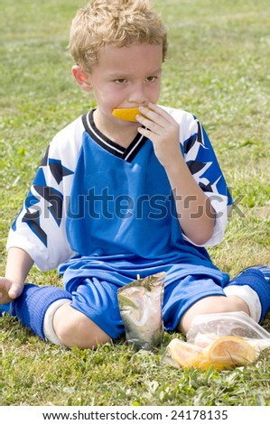 Young soccer player eating orange during halftime - stock photo