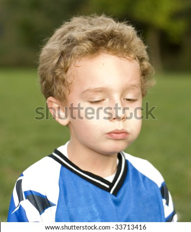 Young soccer player eating snack during halftime - stock photo
