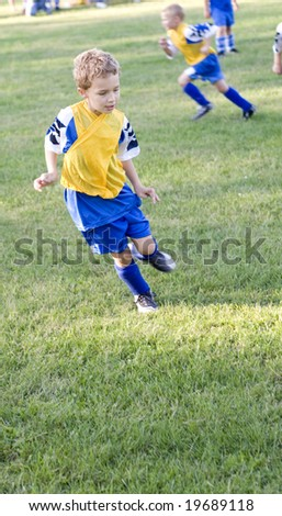 Young soccer player getting in position to steal ball on field - stock photo