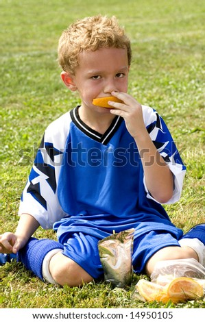 Young soccer player having halftime snack of orange and drink pouch - stock photo
