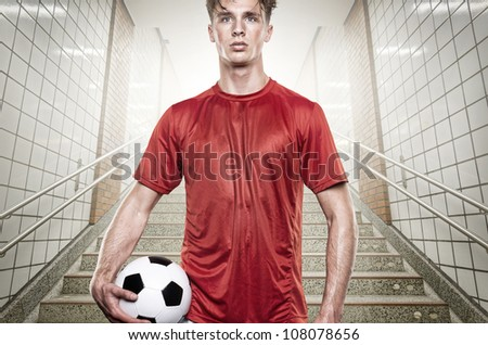 Young soccer player in gray tunnel - stock photo