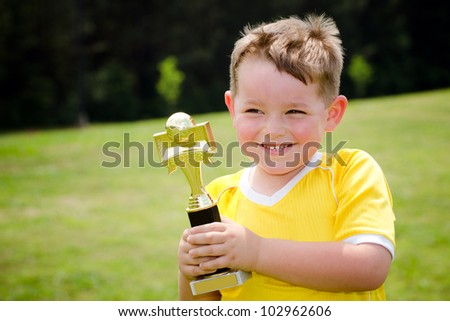 Young soccer player in uniform with his new trophy - stock photo