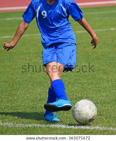 Young soccer player kick off the ball - stock photo