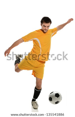 Young soccer player kicking ball isolated over white background - stock photo