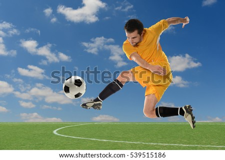 Young soccer player kicking ball outdoors