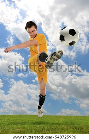 Young soccer player kicking ball outdoors with clouds in background