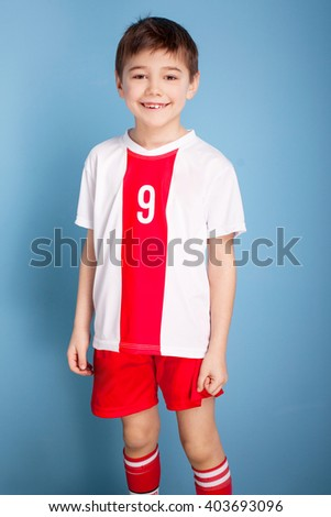 Young soccer player posing on blue background, wearing sportswear - stock photo