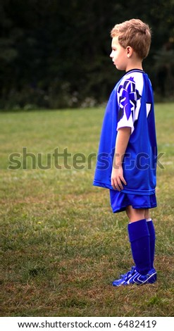 Young soccer player standing on field waiting for game to start - stock photo