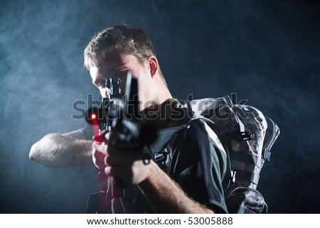 Young soldier aiming with laser M16 gun. - stock photo