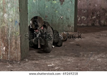 Young soldier behind concrete wall - stock photo