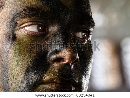 young soldier face with jungle camouflage, outdoor - stock photo