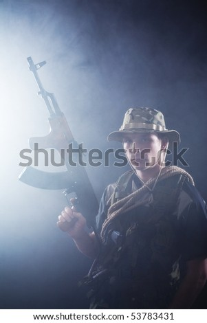 Young soldier holding Kalashnikov ready for combat.