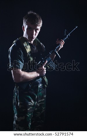 Young soldier in camouflage holding M16 rifle.