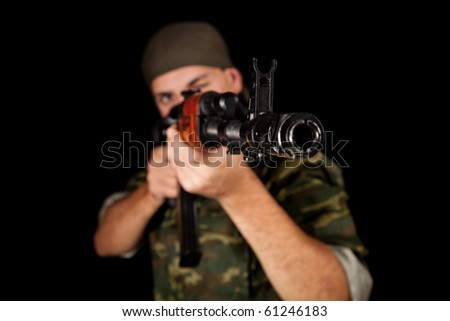 Young soldier in uniform with rifle, selective focus on weapon