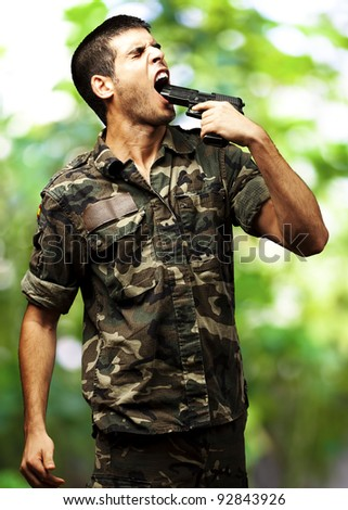 young soldier wearing a jungle camouflage committing suicide against a jungle background - stock photo