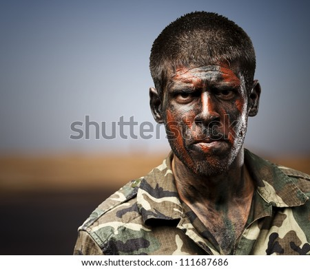 young soldier with camouflage paint looking very serious against a desert - stock photo