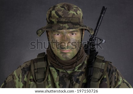 Young soldier with jungle camouflage paint on black background - stock photo