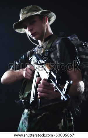 Young soldier with military backpack and Kalashnikov assault rifle looking down.