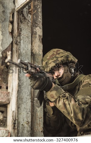 Young soldier with pistol aiming at somebody - stock photo