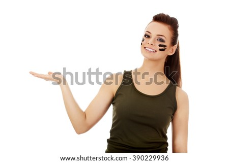 Young soldier woman presenting something on open palm - stock photo