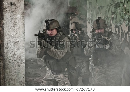 Young soldiers on patrol in smoke - stock photo