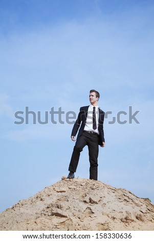 Young solitary businessman standing on a hill in the desert - stock photo