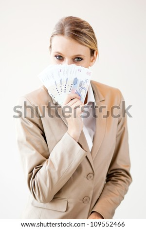 young south african woman holding cash note close to her face - stock photo