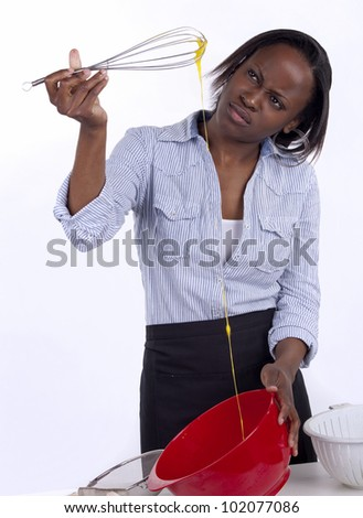 Young South African woman looking confused by the egg she's beating. - stock photo